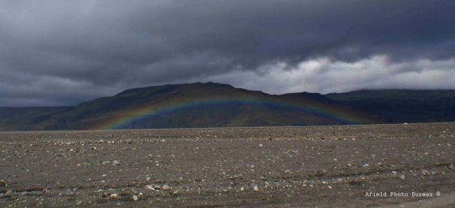 A rainbow arching low over the river.