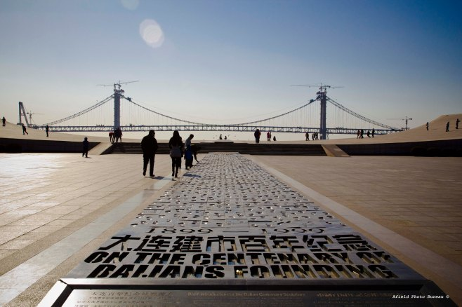 Xinghai Square is the largest city square in the world. On the sea edge of the square lies a sculpture with 1,000 footprints representing       the people's history of Dalian since its founding. Some of the prints show that of bound feet, which must have just been hell for the owners. Xinghai Bay Cross-Sea Bridge in the background.